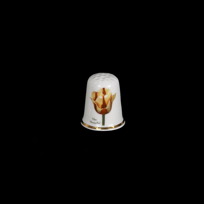 Een porseleinen vingerhoedje met een gouden band en met een botanische afbeelding van de Tulp Flaming Bird
